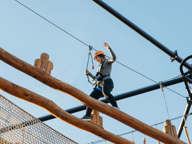 girl on high woodsman challenge at adventure park